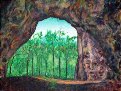 Blick aus einer Höhle heraus auf eine Baumlandschaft. An den Höhlenwänden erscheinen im Spiel von Licht, Schatten und der Felsstrukturen Gesichter und Gliedmaßen von Kreaturen, die beinahe wie lebendige Wesen wirken.