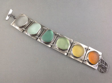 A muted rainbow of well-frosted sea glass on matte sterling plates.
