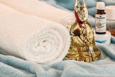 Zwei Handtücher und ein Massageöl. Massage als ergänzendes Angebot bei Verspannungen im Rücken und zur Förderung von Tiefenentspannung.