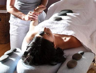 A lady lying on a table receiving a Hahana Hot stone Hawaiian massage to bring relaxation, balance and Harmony