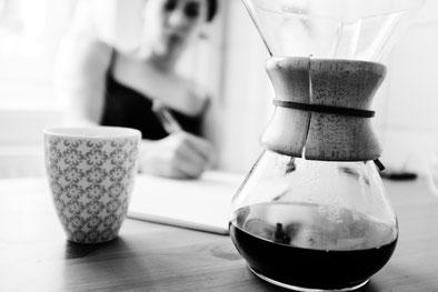 Junge Frau sitzt mit Kaffeebecher und Kanne mit Filteraufsatz a einem Tisch und schreibt mit Hand. (Foto: Barnimages)