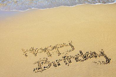"""""""Happy Birthday"""" in den Sand geschrieben, das Wasser rollt leicht im Hintergrund auf den Strand"""