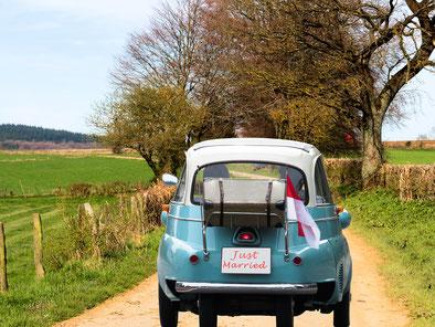 """kleines Auto mit """"just married"""" Schild auf einem Feldweg"""
