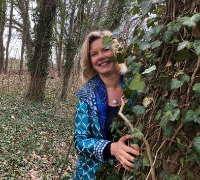 Energetikerin Christina Lechner in hellblauem Mantel umarmt einen Baum, an dem Efeu hochrankt