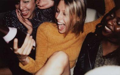 tjejer skrattar och håller i flaska