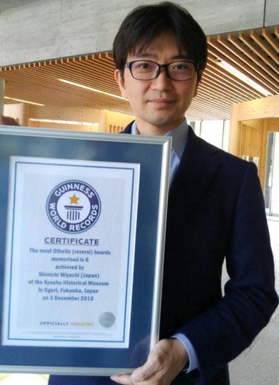 記憶力分野でギネス世界記録樹立。ギネス公式認定証を手に、謙虚に微笑む 記憶術セミナー講師であり高IQ天才集団MENSA(メンサ)の日本人会員 宮地真一(シン)。