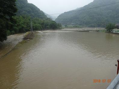 写真奥の堤防が決壊し田んぼが川のように。