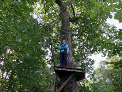 Susanne McCabe pauses and smiles for the camera on a platform on the treetop course.