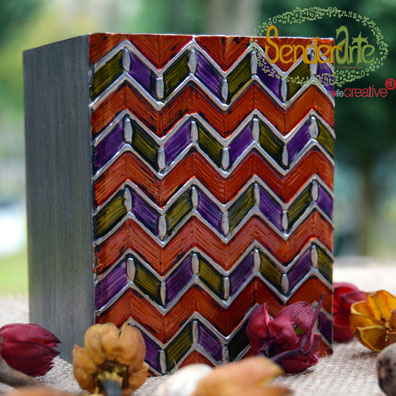 Cubilete con motivos en Zig-Zag repujados en estaño. Madera de pino teñida y barnizada, interior naranja, exterior wengué. 8cm. x 8cm. x 10cm. – 25€
