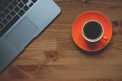 brauner Holztisch mit roter Tasse mit Untertasse und Kaffee, Laptop Tastaturausschnitt