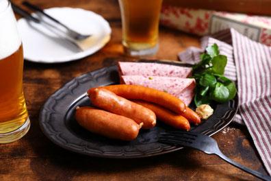 カッティングボードに盛り付けられたチーズと生ハムのおつまみ。フランスパンの輪切りと赤ワイン。