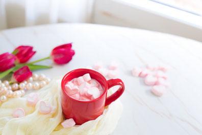 ページの開かれた洋書のうえに置かれた、紅茶の入ったカップ&ソーサ。パステルカラーの春の花。