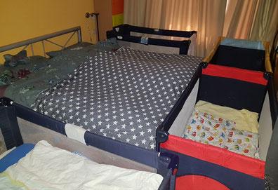 Schlafzimmer mit vier Reisebetten für die Kinder