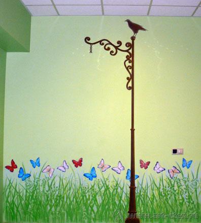 Нарисованный столб поддерживает висящие на стене часы.