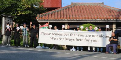オスプレイ事故の犠牲者に哀悼の意を示したハートクリーンプロジェクトの参加者=11日、普天間飛行場の大山ゲート前