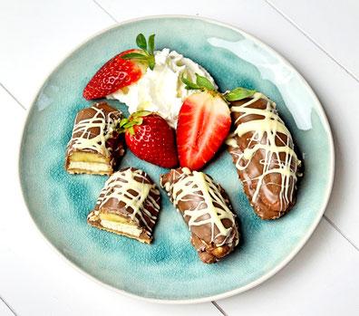Mit Schokolade überzogene Bananen auf feiner Buttercreme und Marzipanmakronen