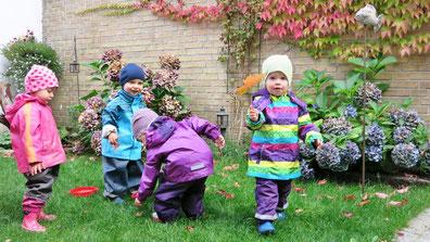 Die Kinder sammeln Herbstblätter