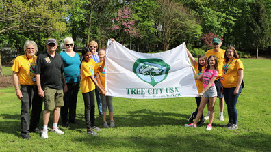 Steve Falco, far right in green hat, with Tree City USA flag April 2019