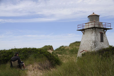 Painting the New London Lighthouse Prince Edward Island. The lighthouse is slowly being walled in by the dunes.