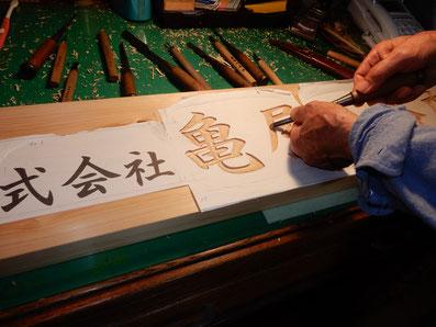 檜の看板製作工程 板にノミで文字を彫る