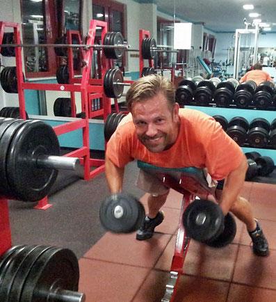 Mann in orangen T-shirt auf dem Bauch liegend mit Kurzhanteln