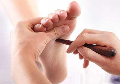 Fußreflexzonen Massage. Der Fuß wird mit einem Holzstäbchen akupunktiert.