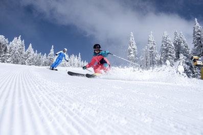 Junger Skifahrer in rotem Anzug beim Abschwung