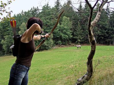 Dame zielt mit dem Bogen auf einen 3D-Hirsch
