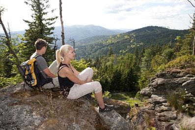 Ein junges Pärchen auf einem Felsen sitzend