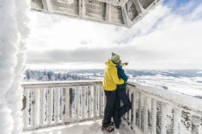 Pärchen steht auf dem vereisten Aussichtsturm Alpenblick