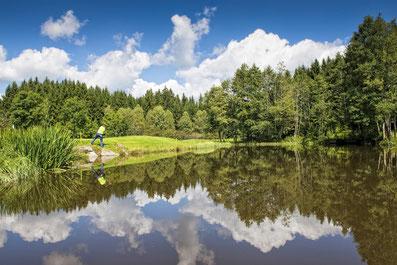 Golfer an einem kleinen See im Vordergrund