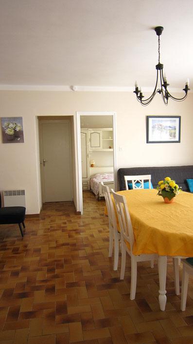 Séjour spacieux de 25 m² avec grande table pour 10 personnes. Vue sur chambre2
