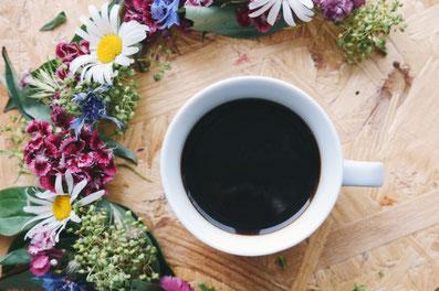 デスクに広げられたビジネスグッズ。パソコンのキーボードの上に置かれたピンクの腕時計。広げられたノートのうえに置かれたピンクのボールペン。ゼムクリップ。メモ帳。ピンクのバラのブーケ。紅茶の入ったカップ&ソーサ。