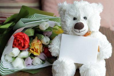 コーヒーの入ったカップ&ソーサと砂時計。緑色の手帳とゴールドのボールペン。無造作に置かれたマーガレットの花束。