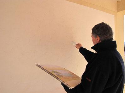 L'artiste peintre s'aide de ses esquisses élaborée pour reporter le motif au crayon sur le mur