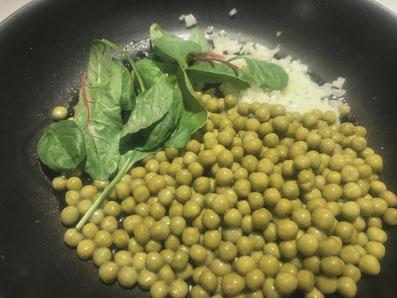 Erbsen, Zwiebeln und Spinat in Sonnenblumenöl schwenken