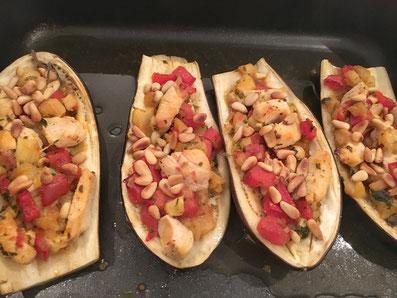 Die Aubergine-Hälften füllen, mit den Pinienkernen besträuen und im Ofen bei 200° 15 Minuten backen