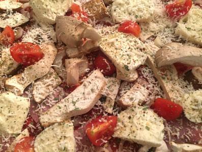 Den Mozzarella und die Tomaten darüber legen, Parmesan darüber raffeln und mit Oregano, Salz und Pfeffer würzen