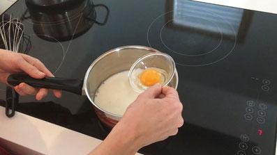 Milch erhitzen und ein Eigelb dazugeben