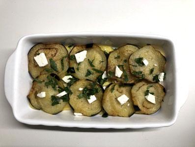 Eine Lage Aubergine darauf legen und ebenfalls salzen, pfeffern und mit Petersilie und Fetawürfel bestreuen