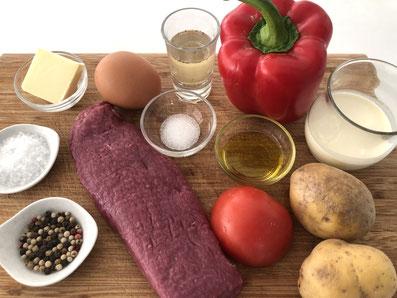 Zutaten: Lamm, Kartoffeln, Paprika, Tomate, Butter, Olivenöl, Ei, Rahm, Bouillon, Zucker, Salz, Pfeffer, Paprikapulver