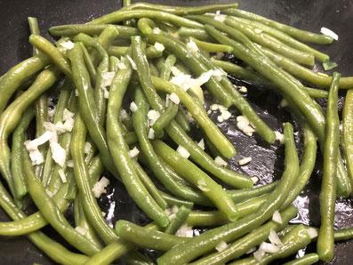 Die Bohnen mit den gehackten Zwiebeln in Butter schwenken und warmstellen