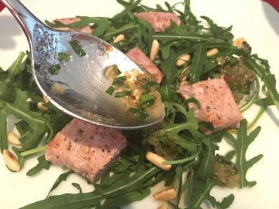 Den Thunfisch auf den Rucola legen und mit der Salatsauce nappieren