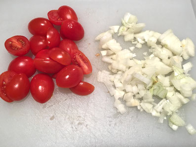 Zwiebeln hacken und Tomaten halbieren