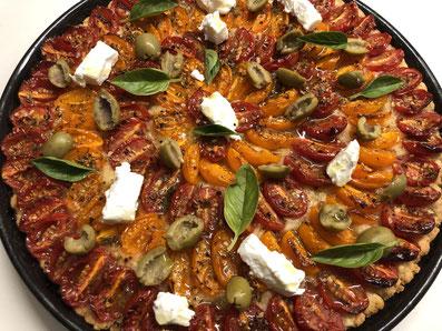 Nach dem Backen mit Ziegen-Frischkäse, Oliven und Basilikum garnieren