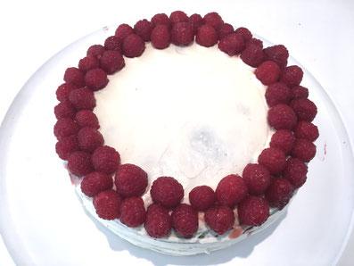 Die Torte mit einem Doppelkranz aus Himbeeren dekorieren