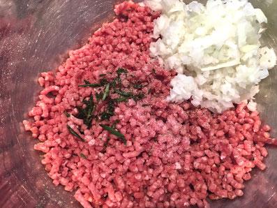 Zwiebel und Kräuter mit der Fleischmasse mischen, salzen, pfeffern
