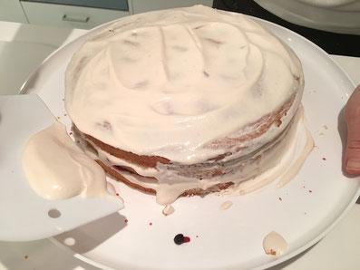 Nun mit einem Spachtel die Torte mit der restlichen Crème bestreichen