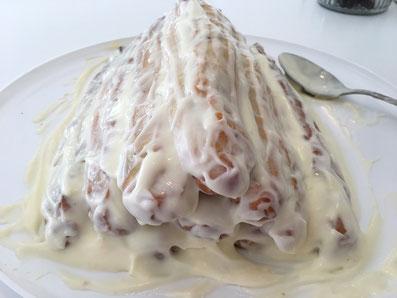 Den Giebel darauf setzen, alles noch einmal mit der Crème bestreichen und den Kuchen zugedeckt in den Kühlschrank stellen