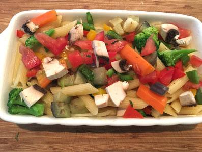 Die vorgekochten Teigwaren und das vorgekochte Gemüse in die Gratinform schichten